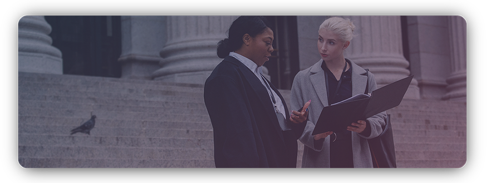 Woman and female lawyer talking outside of a courthouse